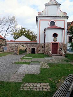 Dva druhy dlažby s trávníkem před kaplí v Dobřichovicích